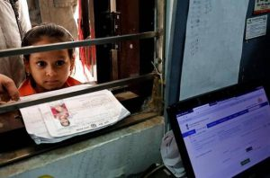 1.नवी दिल्ली येथील आधार नोंदणी केंद्रात आपला क्रमांक येण्याची वाट पाहत उभी असलेली एक लहान मुलगी. सौजन्य: Reuters/Files