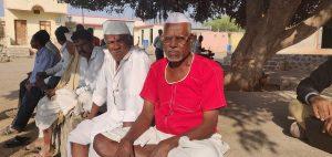 साताऱ्यातील गंगोटी गावामध्ये रामहरी झिम्मर (लाल कपड्यांमध्ये). या गावातील जवळजवळ सर्व प्रौढ व्यक्ती त्यांच्या गुरांसह चार किलोमीटर अंतरावर असणाऱ्या गुरांच्या छावणीमध्ये स्थलांतरीत झाल्या आहेत. फोटो: सुकन्या शांता