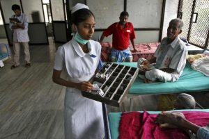 चेन्नई येथील राजीव गांधी गव्हर्नमेंट जनरल हॉस्पिटलमधील वॉर्डमध्ये रुग्णांना सरकारद्वारे पुरवलेली मोफत औषधे देताना कर्मचारी, १२ जुलै २०१२. श्रेय: रॉयटर्स/फाईल्स