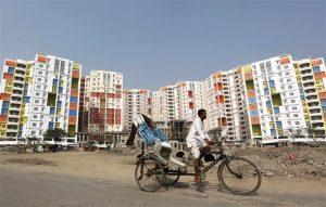 कोलकता शहराच्या बाह्य भागातील एका नव्याने बांधलेल्या इमारतीच्या बाहेर एक माणूस आपली सायकल रिक्षा चालवताना. दिनांक : २९ डिसेंबर २०१०. सौजन्य : रॉयटर्स / रूपक दे. चौधरी