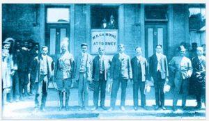 """1903 जोहान्सबर्ग येथील वकिली कचेरीच्या बाहेर आपल्या सहकार्यांसोबत गांधी (डावीकडून तिसरे). कचेरीसाठी जागा शोधताना गांधी म्हणाले होते, """"भारतीय व्यक्तीला सोयिस्कर वस्तीत कचेरीसाठी जागा मिळणं तिथं अवघडच होतं."""""""